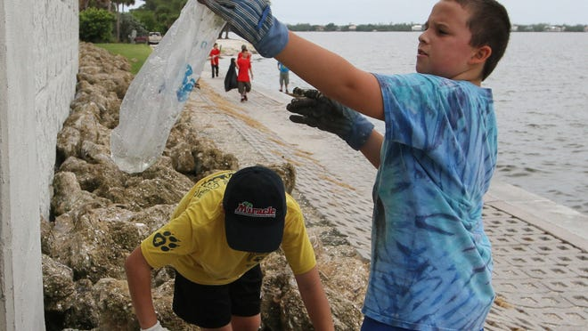 Alex Hessner, 10, right, and Alex Tardie pick up trash around the Sanibel Causeway during cleanup.