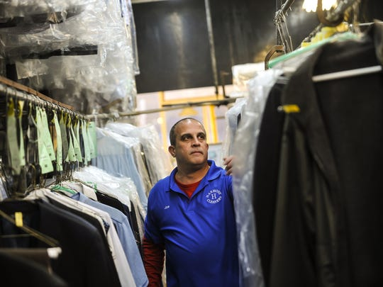 Joe Cruz, owner of Harmony Cleaners, looks for clothing prepared for a customer in Middletown.