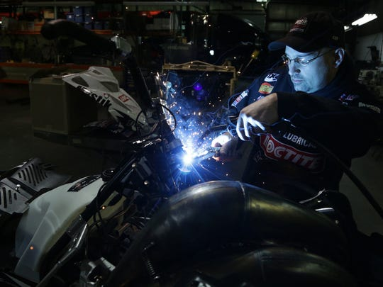 A mechanic welds a bracket at Polaris Industries in