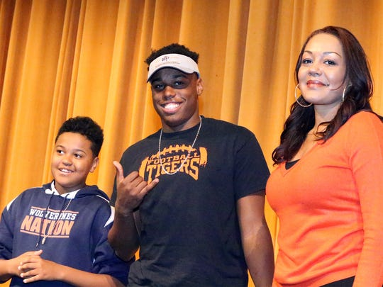 Javaughn Thomas, center, of El Paso High flashes the Miners pick after signing to play football for UTEP with mother Judith Perez, right, and brother Markeel Thomas, 12, Wednesday in El Paso High's auditorium.