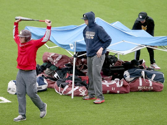 South Kitsap High School baseball players use a cover for their gear in the rain while getting ready for batting practice at the football stadium. The team is using the turf field since their field is unplayable.