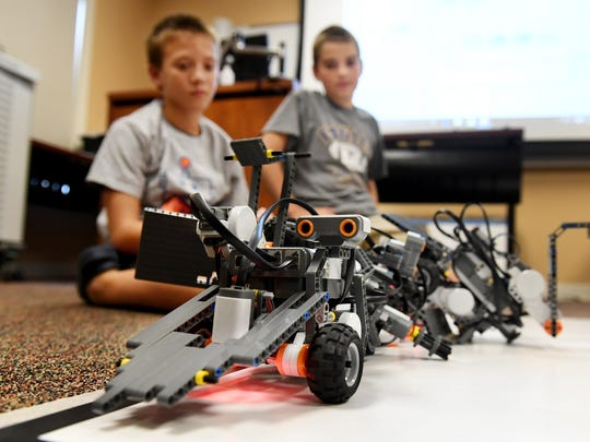 Aiden Swanger and Nash Poberson watch as their robots