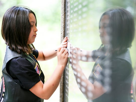 Nya Vargas makes a charcoal rubbing of her uncle's name, SPC Eric. S. McKinley, from the wall of the Afghan-Iraqi Freedom Memorial following a Memorial Day service on Monday, May 30, 2016. McKinley served in the Oregon Army National Guard and was killed in 2004 by a roadside bomb north of Baghdad.