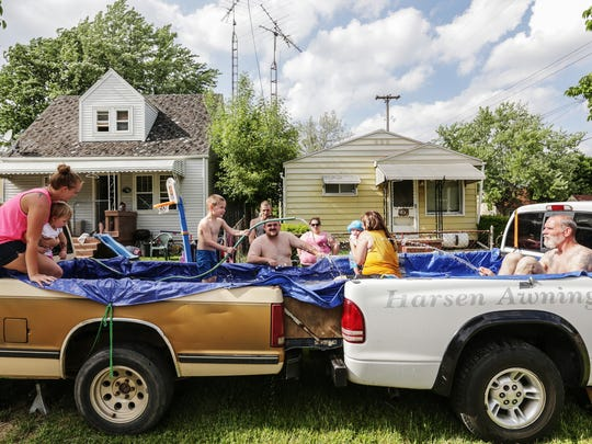 'I contemplated buying a pool and I always wanted to try putting a tarp to put a pool in the back of a truck. It was cheaper so we did it this way,' Frank Evans (center) 24, of Flint said while enjoying their pool made using his truck and a neighbor's on the front lawn of their houses Thursday, May 26, 2016 on the south side of Flint.