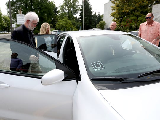 Mayor Chuck Bennett takes the ceremonial first ride of an Uber in Salem at the Oregon State Capitol in on Wednesday, June 7, 2017.