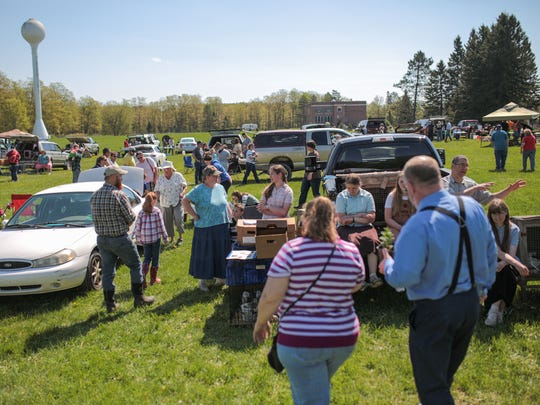 People gather in a field next to the Holmquist Feed Mill in Trenary in Michigan's Upper Peninsula during the Trenary Fur and Feather Swap in Trenary on Saturday May 27, 2017.