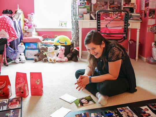 "Bella Simons, 17, laughs while sitting amongst a poster board and candy bags she is preparing for her ""Spa Night"" fundraiser, at her home in Carmel, Ind., Wednesday, Jan. 3, 2017. Simons underwent brain surgery and radiation treatment for two non-malignant but potentially deadly tumors in 2015, and November last year, suffered a stroke caused by radiation. She will undergo brain surgery again at Riley Hospital for Children on January 11 in hopes of preventing a future stroke. Simons and her mother Tasha will give back to Riley Hospital by hosting a ""Spa Night"" fundraiser at Saks Fifth Avenue on January 9, raising money for the Carmel Dance Marathon, which benefits Riley Hospital for Children."