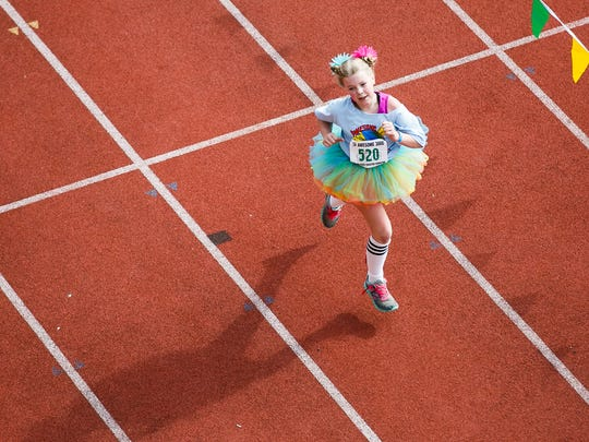 Fourth grader Elia Dowers runs towards the finish line at the 36th annual Awesome 3000 on Saturday, May 5, 2018, at McCulloch Stadium in Salem, Ore.