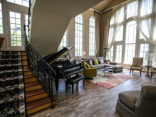 The great room is 2 1/2 stories tall with three rows of windows and views on three sides. Because this spot needed the staircase, the stairs were built floating style to interrupt the view less.