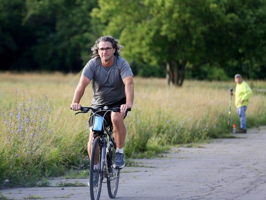 Tom Leeper, 51, of Berkley rides his bike along a street