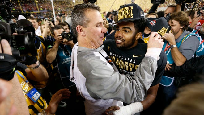 Ohio State coach Urban Meyer congratulations running back Ezekiel Elliott after beating Oregon on Monday in college football's national title game. Elliott's mother, Dawn, was a multi-sport Iowa high school star at Mount Ayr.