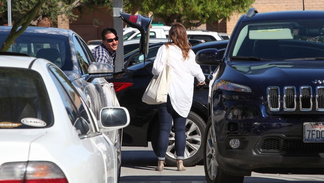 A driver picks up a woman who was carrying luggage from the airport in the parking lot at Palm Springs City Hall, November 2, 2016.