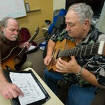 Guitar teacher, Douglas Morgan, left, gives veteran Mike Dummond, right, personalized guitar instructions during a Veterans Administration outreach program call Guitars for Vets. The program, opened to qualified vets, gives the participants free lesson and guitars.