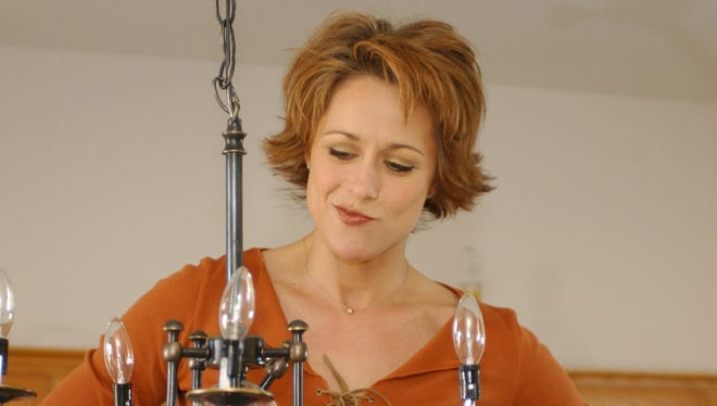 'Trading Spaces' host Paige Davis examines a ceiling lamp she accidentally damaged while taping of an episode in Las Vegas in 2003.