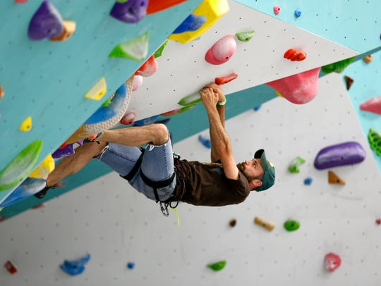 Ryan McClain climbs a bouldering problem on a wall