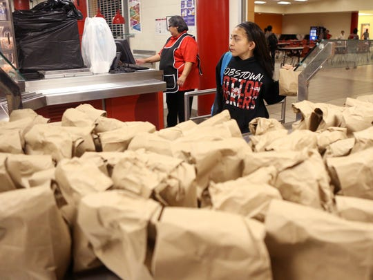 Seale Junior High School student Amelynne Olguin, 11, picks up a dinner bag at the school on Sept. 28, 2017. The Robstown Independent School District began an after-school dinner program this year that provides free meals for students.