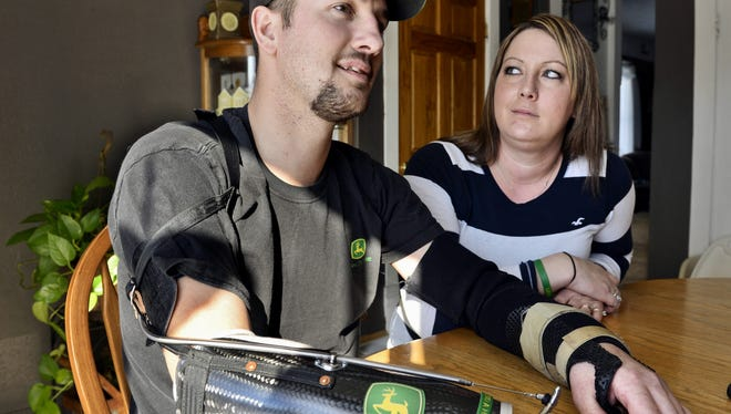 In this Feb. 25, 2014, photo, Little Falls, Minn., resident Jamie Houdek, with his wife, Lisa, at his side, talks about his recovery after he lost his right hand to a corn picker in November 2013 on the 60-acre hobby farm where he raises beef cattle. The nation's growing embrace of small-scale production of local and organic crops is leading to more farm injuries and deaths among amateur growers. Experts say some novices have little appreciation of the occupation's dangers.