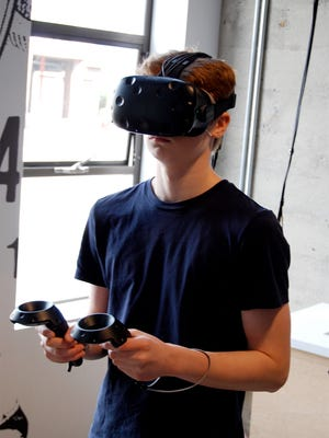 The virtual reality exhibit involves the headgear and wands for each hand.