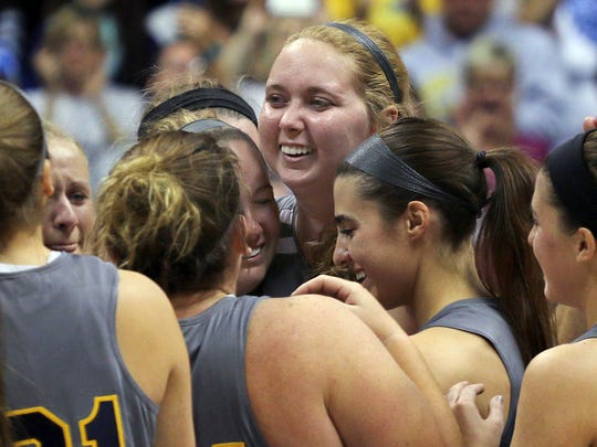 FILE - In this Nov. 2, 2014, file photo, Mount St. Joseph's Lauren Hill, center, gets congratulated by teammates after scoring during her first NCAA college basketball game against Hiram University at Xavier University in Cincinnati. The 19-year-old freshman basketball player died at a hospital in Cincinnati Friday, April 10, 2015, the co-founder of her foundation The Cure Starts Now said. (AP Photo/Tom Uhlman, File)