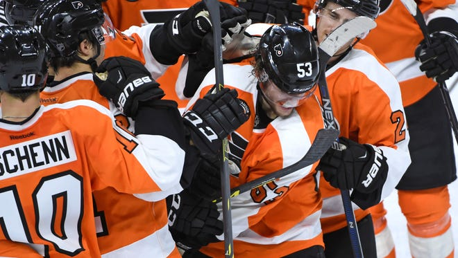 Shayne Gostisbehere (53) is mobbed by teammates after scoring game winning goal against the Carolina Hurricanes.