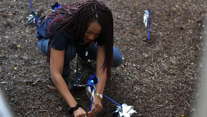 Jaleesha Rundell places a pinwheel in the ground Wednesday outside the Department of Children & Family Services Rapides office.