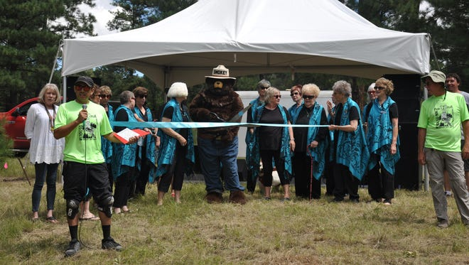 Smokey Bear cuts the ribbon during the opening of the new trail system at Cedar Creek in Ruidoso.