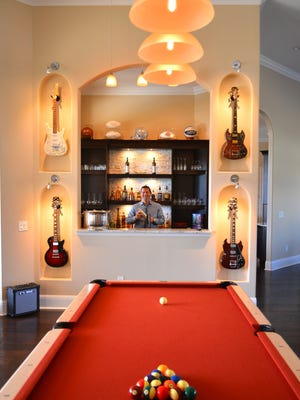 David Cohen at the bar in his game room, with pool table, huge flatscreen televison, pool table and guitar collection. David Cohen's Lansing Island home was built for entertaining, with large spacious rooms and sliding pocket doors that open up with no divider, seamlessly merging the living area with the pool and patio.