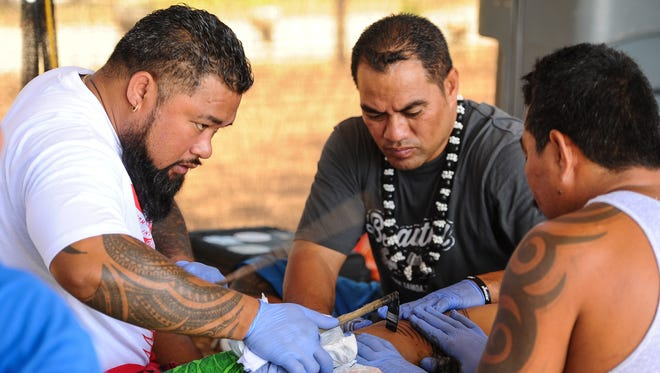 Independent State of Samoa master tattoo artist Su'a Sulu'ape Peter, left, is assisted by tattoo apprentices Tautai Pati Levasa, center, and Pati Taua Vili during a demonstration in the art of traditional tattooing at the Sagan Kattoran Chamoru cultural center in Tumon on Tuesday, May 24.