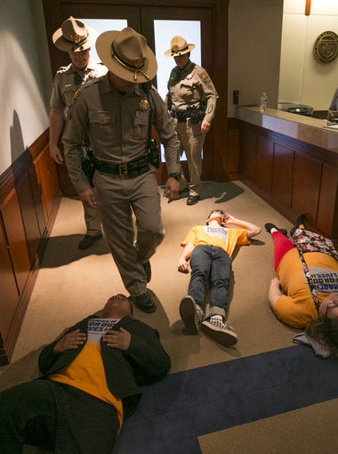 """DPS troopers walk over high school students Jacob Martinez of Dobson High, Jordan Harb of Mountain View and Dawn Motley of Mountain View as they participate in a """"die-in"""" in the lobby of Governor Doug Ducey's office during a protest organized by the """"March for Our Lives"""" movement  at the Arizona Capitol in Phoenix on April 20, 2018."""