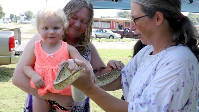 Betsey Hempel holds a python out so Theresa Lang and her granddaughter, Mary Lindsey, 2, can touch the snake on Saturday, Aug. 29, during the Learn & Care event at the Pay It Forward Fort Smith food pantry, 616 N. 10th St. Betsy and her husband, Derek Hempel, own Jungle Mans Outreach in Van Buren and brought young pythons and African Pixie Frogs to the event to share with everyone.