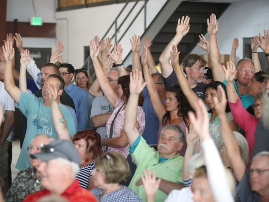 Ledgeview electors with hands raised vote in favor of the town's purchase of the Ledgeview Golf Course on Tuesday.