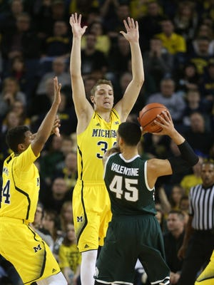 Michigan's Mark Donnal defends Michigan State's Denzel Valentine during the first half on Tuesday, February 17, 2015 at Crisler Center in Ann Arbor.