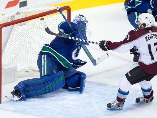 Colorado Avalanche's Alexander Kerfoot (13) tries to get his stick on the puck next to Vancouver Canucks goalie Anders Nilsson, of Sweden, during the second period of an NHL hockey game Tuesday, Feb. 20, 2018, in Vancouver, British Columbia. (Darryl Dyck/The Canadian Press via AP)