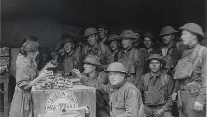 """A Salvation Army """"doughnut girl"""" serves  doughnuts to soldiers during World War I."""