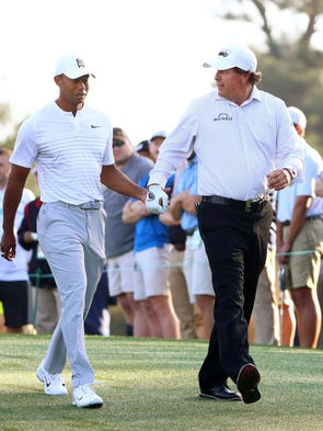 Tiger Woods and Phil Mickelson walk off the 10th tee