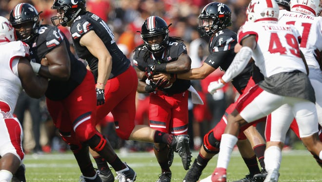 Cincinnati Bearcats running back Mike Boone (5), center, looks for running room as the offensive line blocks in the first quarter during the college football game between the Miami University RedHawks and the Cincinnati Bearcats , Saturday, Sept. 24, 2016, at Nippert Stadium in Cincinnati.