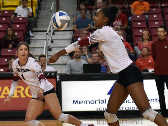 New Mexico State's Tatyana Battle goes for the ball as Aggie Setter Briana Ainsworth get ready for the pass. Both Battle and Ainsworth were named Academic All-WAC honorees.