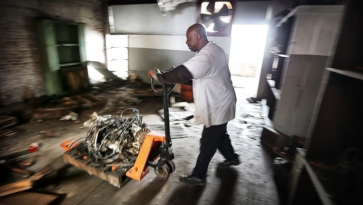 A salvage crew works to remove scrap metal and usable