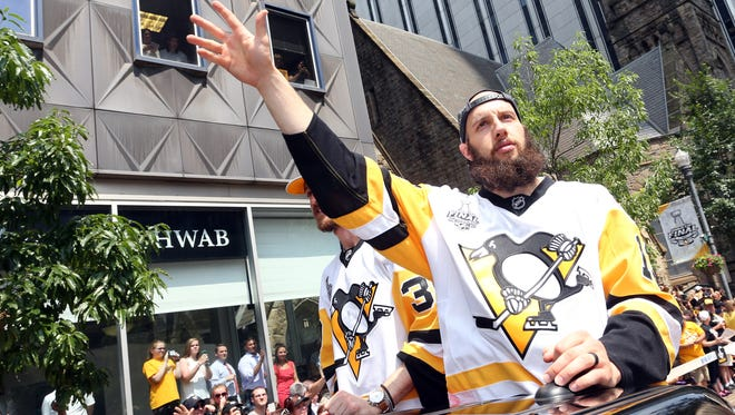 Pittsburgh Penguins center Nick Bonino waves to the fans during the Stanley Cup championship parade and rally in downtown Pittsburgh on June 14, 2017.