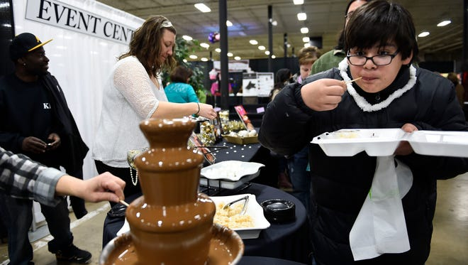 Nic Blair, 13, of Maryville tastes a chocolate marshmallow from the Grande during Chocolatefest Knoxville on Jan. 31, 2015, at the Knoxville Expo Center. Proceeds from the event benefited Knoxville's Ronald McDonald House.