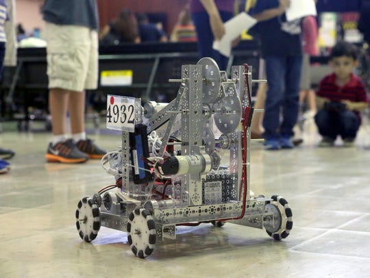 A robot from Moody High School is moved around by students