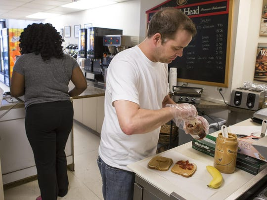 Scott Hines makes sandwiches in his shop across from the DuPont Building in Wilmington on Wednesday.