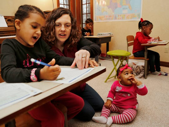 Carlee Dawodu helps her daughter Keziah, 6, with capitalization Wednesday, December 17, 2014, in their Lafayette home. Dawodu's other daughters Elizabeth, 4, background right, and Debjani, 10, background, work on their lessons as youngester daughter Eden, 9 months, plays on the floor. With a gap in he ages of all four of her daughters, Dawodu prefers homeschooling as a way to keep the children together.