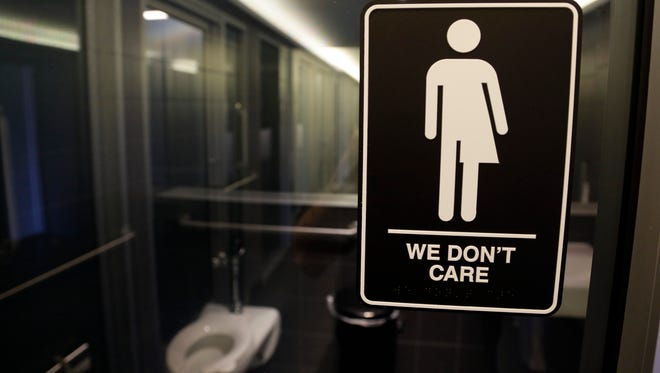 A restroom sign at a private business says both men and women are allowed to use it. Such signs emerged in North Carolina after the legislature in 2016 and 2017 passed laws that stopped local governments from passing anti-discrimination ordinances for LGBTQ people. As of Dec. 1, this ban on such anti-discrimination ordinances was terminated.