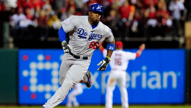 Dodgers right fielder Yasiel Puig rounds second base after hitting a triple during the NLDS at Busch Stadium.
