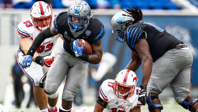 Memphis running back Patrick Taylor, Jr. (left) scrambles past the SMU defense for a first down during second quarter action in Memphis, Tenn., Saturday, November 18, 2017.