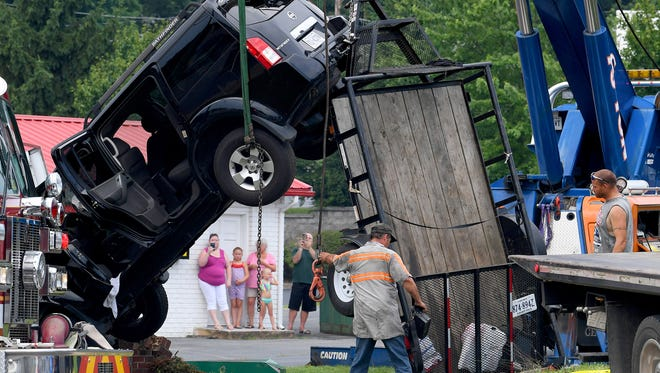 A crane holds a Nissan Pathfinder secure so the trailer it was hauling can be safely removed at the scene of a one vehicle wreck on Greenville Avenue in Staunton on Wednesday, July 4, 2018. The SUV struck a fire hydrant and then a business sign before its trailer pushed the rear of the vehicle up into the air and held it there.