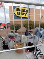 Shoppers take a nap outside Best Buy as they wait for