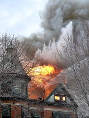 Muscatine firefighters douse flames from above Tuesday, Dec. 1, 2015, as fire spits out the top of the Huttig mansion near downtown Muscatine, Iowa.