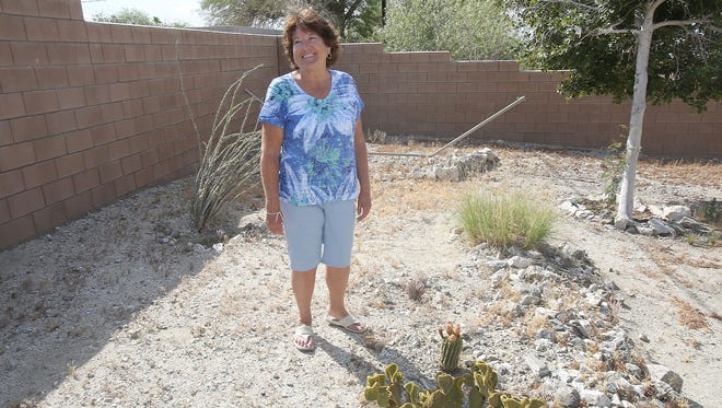 Karen Ragan explains why she thinks a yard of water-thirsty grass is unnecessary in the Coachella Valley's desert climate at her Desert Hot Springs home on Monday.